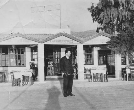 1942. Ο Γιάννης Αντωνόπουλος μπροστά στο μαγαζί του, όταν ακόμη δεν είχε κτιστεί το ξενοδοχείο.